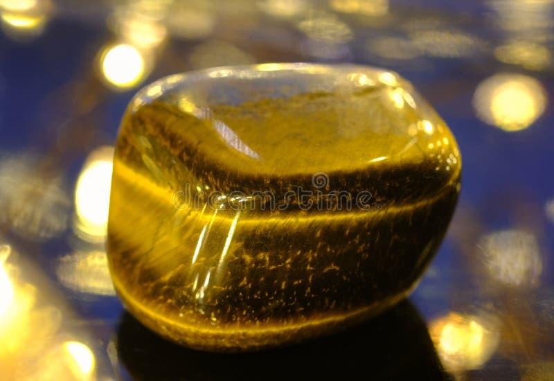 Polished tiger eye stone. On a lumonous background royalty free stock photo