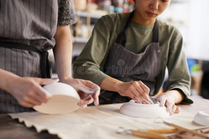 Polishing clay plates. Close-up of busy women in aprons using sandpapers to polish clay plates while working in pottery workshop royalty free stock images