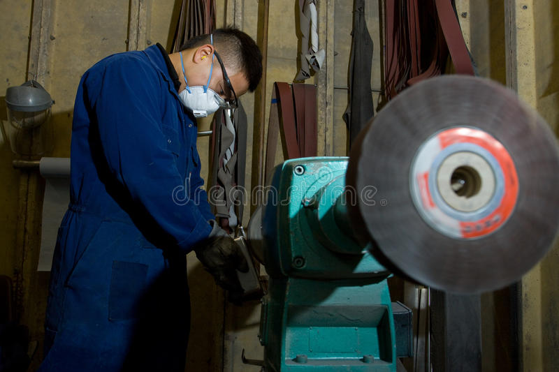 Polishing metal in workshop. Man using electric polisher on stainless steel box in workshop stock photography