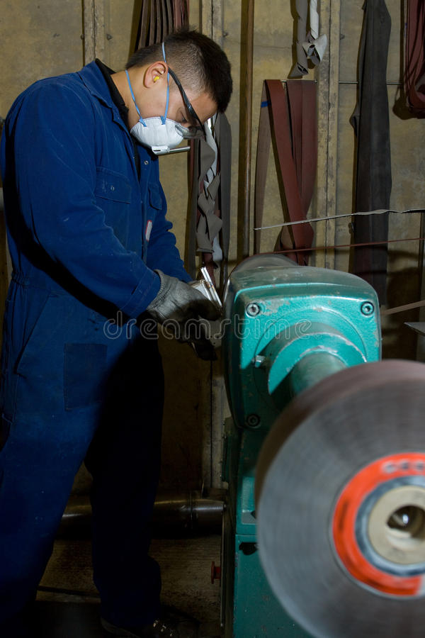 Polishing metal in workshop. Man using electric polisher on stainless steel box in workshop royalty free stock photo