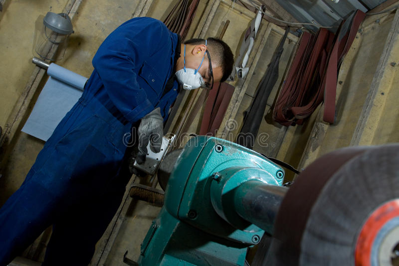 Polishing metal in workshop. Man using electric polisher on stainless steel box in workshop stock photos
