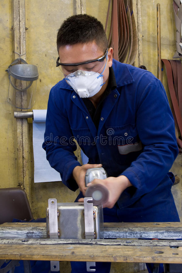 Polishing metal in workshop. Man using electric polisher on stainless steel box in workshop royalty free stock image