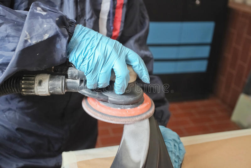 Polishing. Painter polishs a car body component stock photography