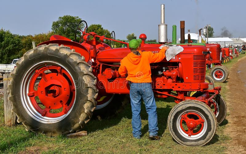 Polishing a restored H Farmall tractor. ROLLAG, MINNESOTA, Sept 1, 2017: An unidentified man polishes a restored H Farmall tractor displayed at the annual WCSTR stock images