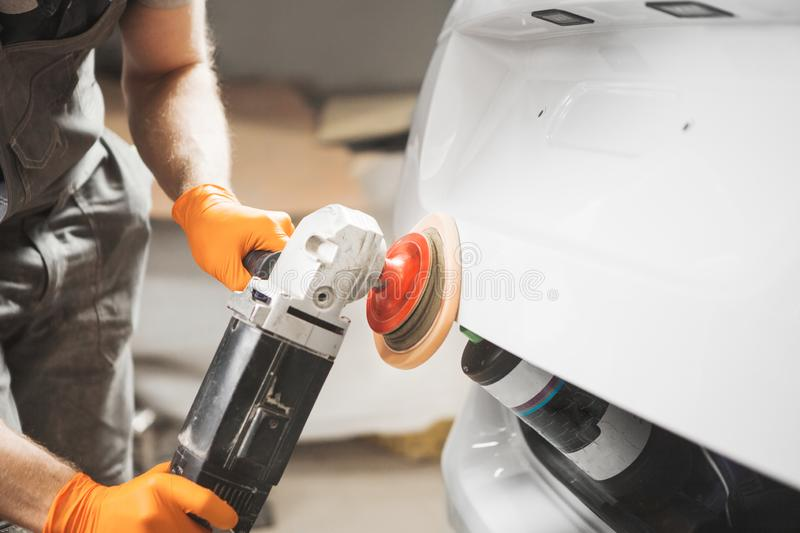 Polishing of varnish after painting the car, close-up. Grinding machine for body of auto. Technology repair and recovery stock photography