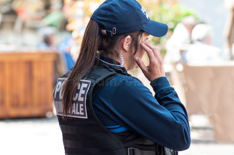 Poliskvinnor observera i huvudsakligt ställe med hörlurar med mikrofon fotografering för bildbyråer