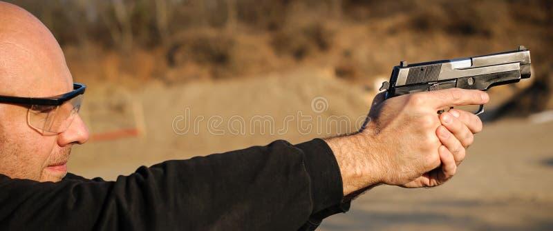 Polismedel och livvakt som pekar pistolen för att skydda från angripare royaltyfria bilder