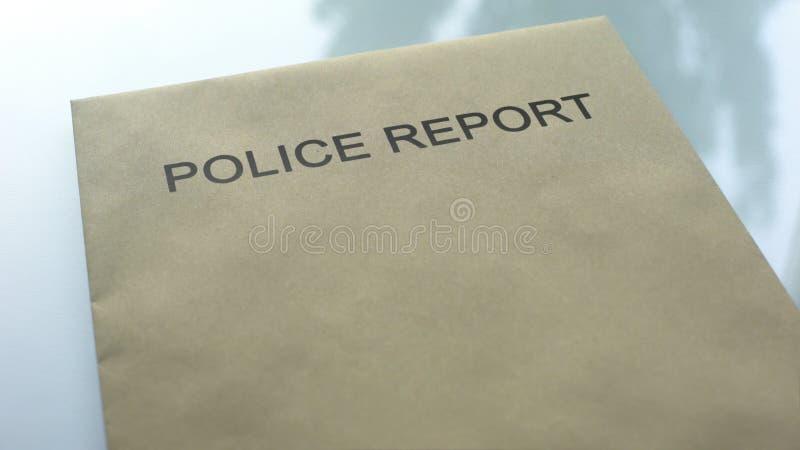 Polisrapport, mapp med viktiga dokument som ligger på tabellen, utredning royaltyfri fotografi