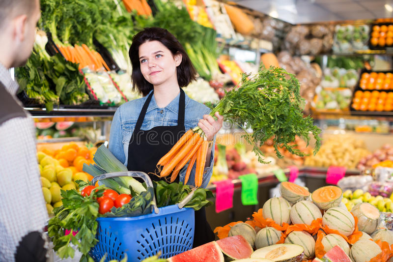 Polite female seller assisting customer to buy fruit and vegetables in grocery shop. Polite female seller assisting customer to buy fresh fruit and vegetables in royalty free stock photos