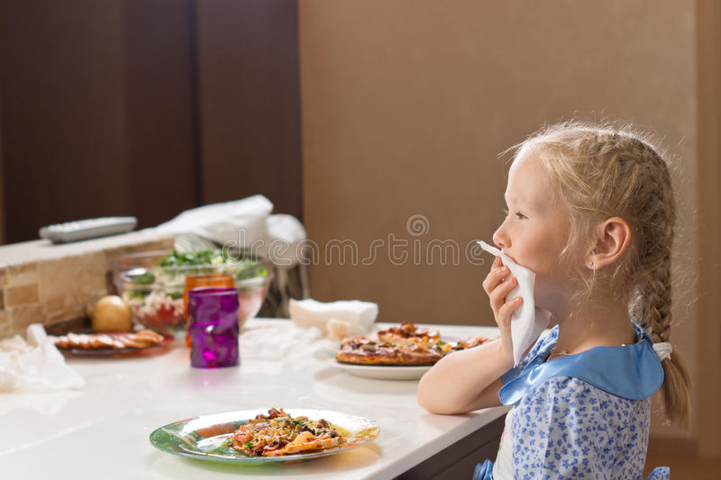 Polite little girl eating homemade pizza. Polite little girl with her blond hair in braids eating homemade pizza sitting at the table carefully wiping her mouth royalty free stock photos