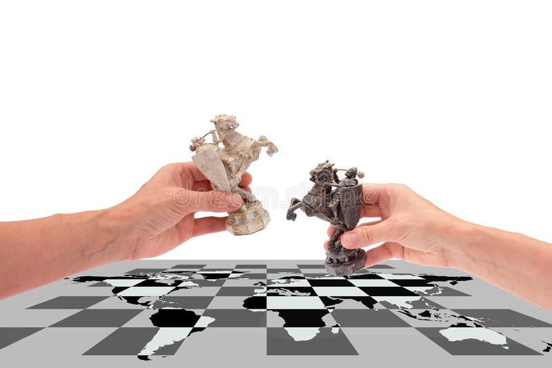 Political games, conceptual collage. Hands hold two chess pieces of a horse, placing them on a chessboard with a world map, isolated on a white background with stock photo