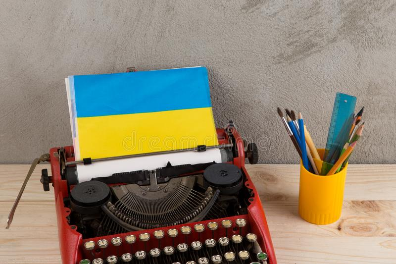 Political news and education concept - red typewriter, flag of the Ukraine, stationery on gray cement background stock photos
