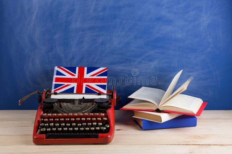 Political, news and education concept - red typewriter, flag of the United Kingdom, books on table. Against the background of the blue school board stock photo