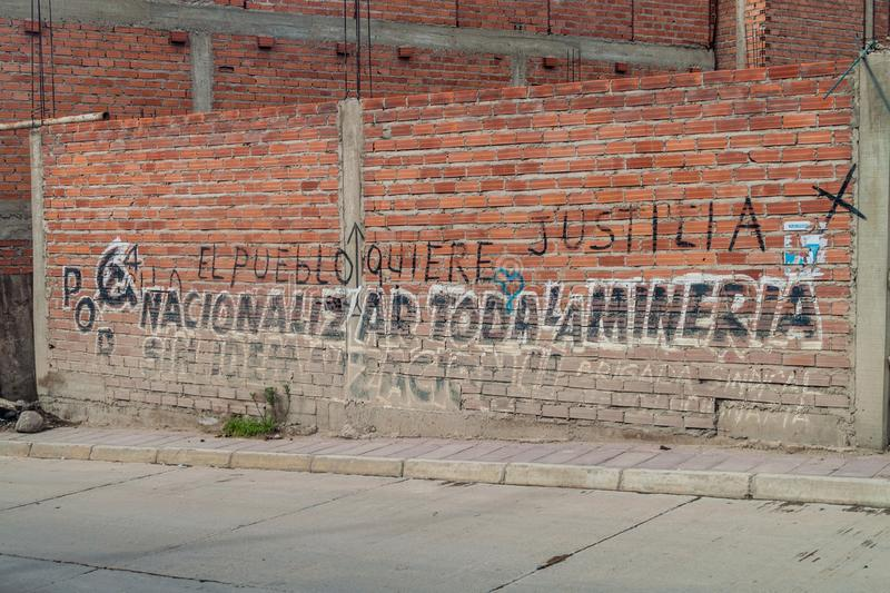 Political text on a wall in Potosi, Bolivia. It says: Peoples want the justice. Nationalize all minin stock image