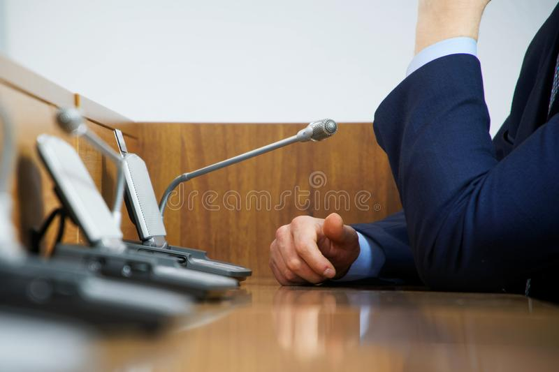 A politician or businessman in a suit sits at a polished wooden table in front of a microphone during a discussion, duty, or royalty free stock photos