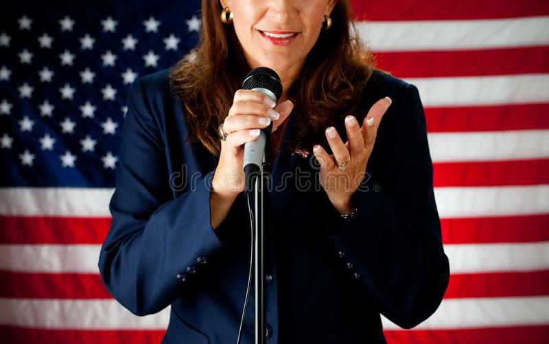 Politician: Cheerful Politician Talking on Microphone. Series with an adult female in a suit, playing the part of a United States politician. Different props stock images