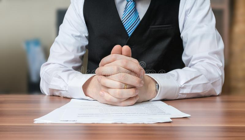Politician with clapsed hands sitting behind desk stock photography