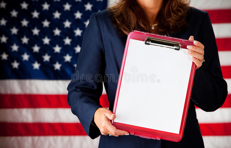 Politician: Clipboard with Blank Paper. Series with an adult female in a suit, playing the part of a United States politician. Different props provide a variety stock photo