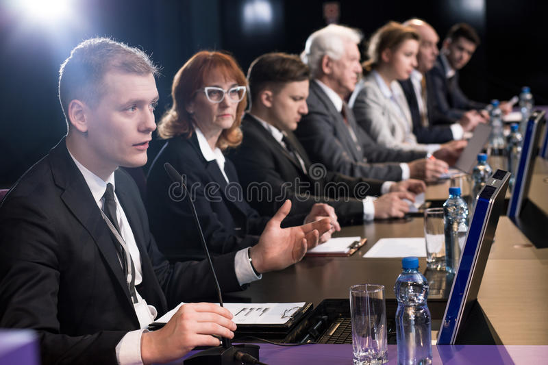 Politician debating at auditorium. Politician debating at a desk with microphones royalty free stock photography