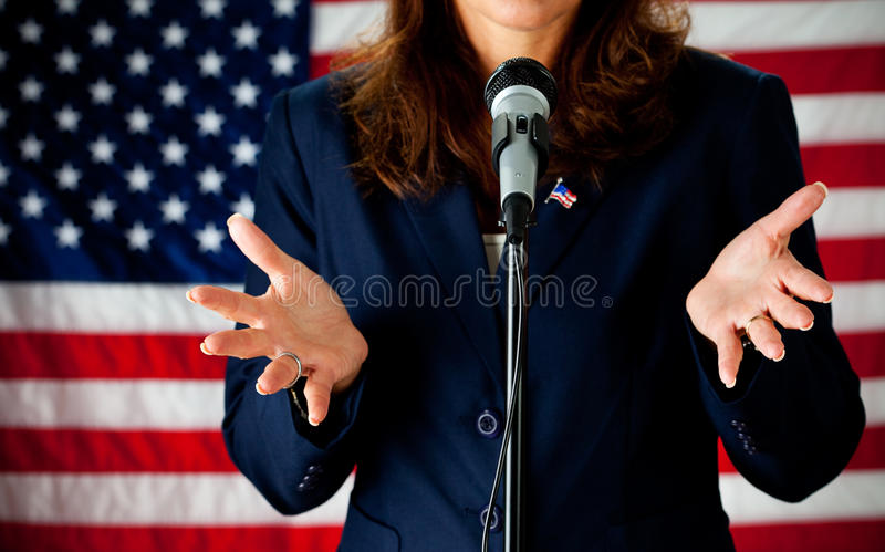 Politician: Giving a Speech. Series with an adult female in a suit, playing the part of a United States politician. Different props provide a variety of concepts royalty free stock images