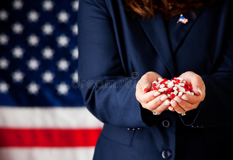 Politician: Handful of Medicine Capsules. Series with an adult female in a suit, playing the part of a United States politician. Different props provide a stock photo