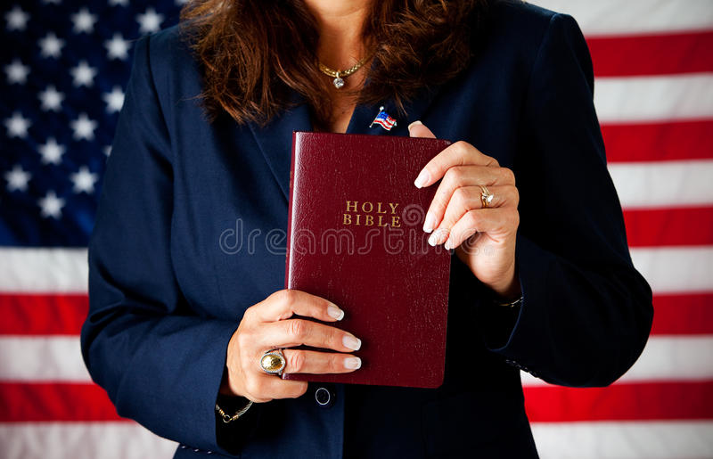 Politician: Holding a Bible. Series with an adult female in a suit, playing the part of a United States politician. Different props provide a variety of concepts stock image