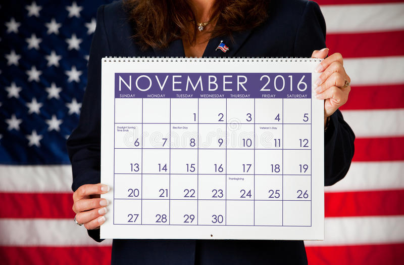Politician: Holding a Calendar with Election Day 2016. Series with an adult female in a suit, playing the part of a United States politician. Different props royalty free stock photo