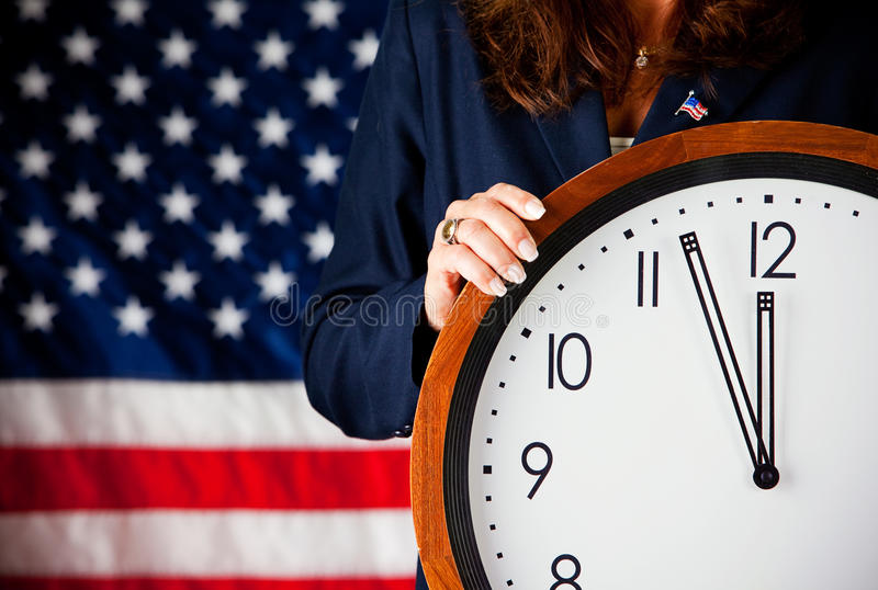 Politician: Holding a Clock. Series with an adult female in a suit, playing the part of a United States politician. Different props provide a variety of concepts stock photo