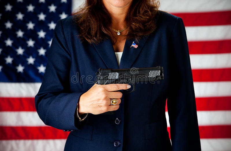 Politician: Holding a .45 Gun. Series with an adult female in a suit, playing the part of a United States politician. Different props provide a variety of stock photography