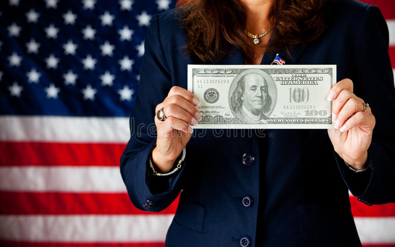 Politician: Holding a Large Hundred Dollar Bill. Series with an adult female in a suit, playing the part of a United States politician. Different props provide a royalty free stock photos