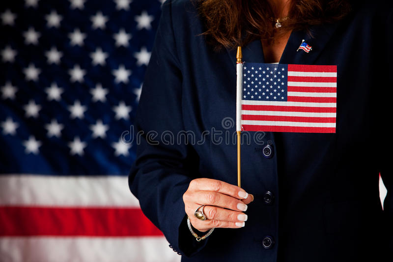 Politician: Holding a Small US Flag. Series with an adult female in a suit, playing the part of a United States politician. Different props provide a variety of stock photography