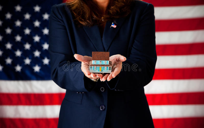Politician: Holding a Tiny House. Series with an adult female in a suit, playing the part of a United States politician. Different props provide a variety of royalty free stock images