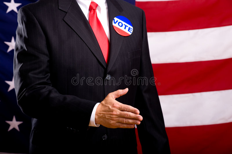 Politician Shaking Hands. A politician in a blue suit and red necktie extending his hand to be shaken. Standing in front of an American flag. shallow depth of stock photo