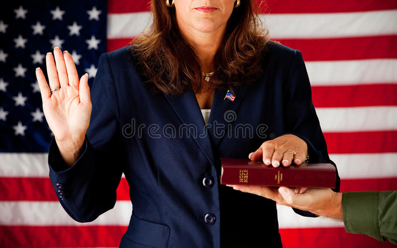 Politician: Woman Taking an Oath on the Bible. Series with an adult female in a suit, playing the part of a United States politician. Different props provide a royalty free stock photo