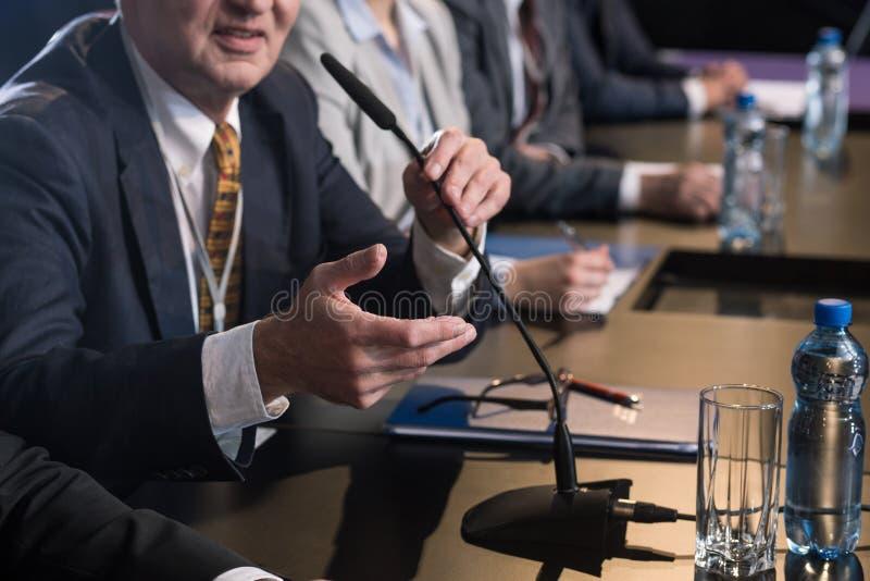 Politico che parla con microfono fotografia stock