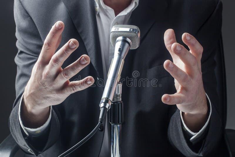 Politico o uomo d'affari maschio che presenta un argomento al suo pubblico fotografie stock