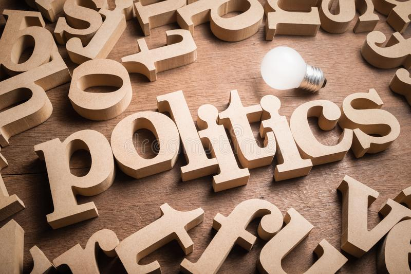 Politics Topic and Bulb. POLITICS wood word in scattered wood letters with glowing light bulb royalty free stock photos
