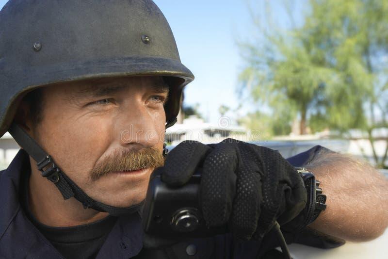 Politieagent die Walkie-talkie in openlucht met behulp van stock afbeelding