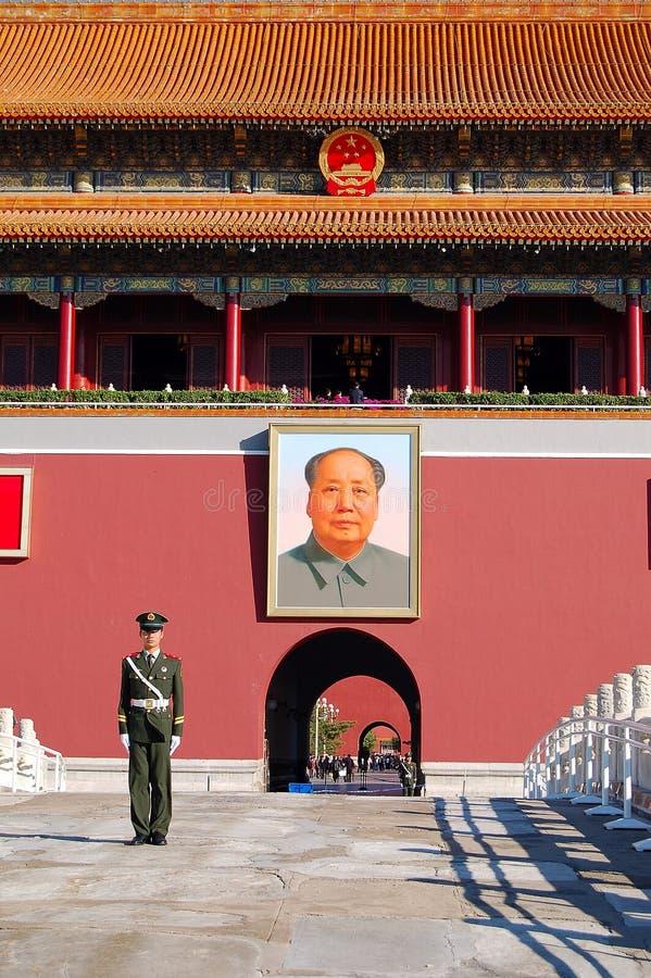 Politieagent en het portret van Mao stock foto
