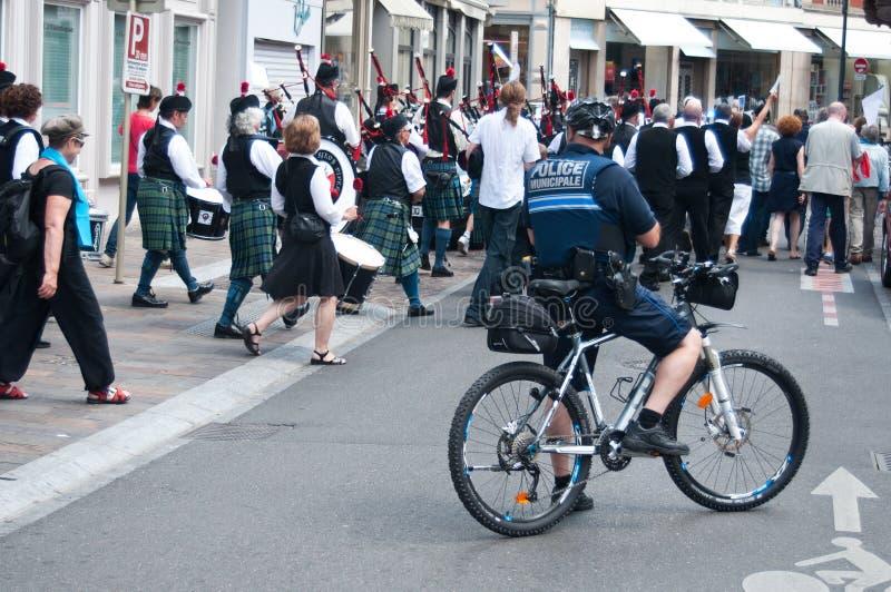 Politieagent in fiets tijdens de demonstratie voor vrede stock fotografie