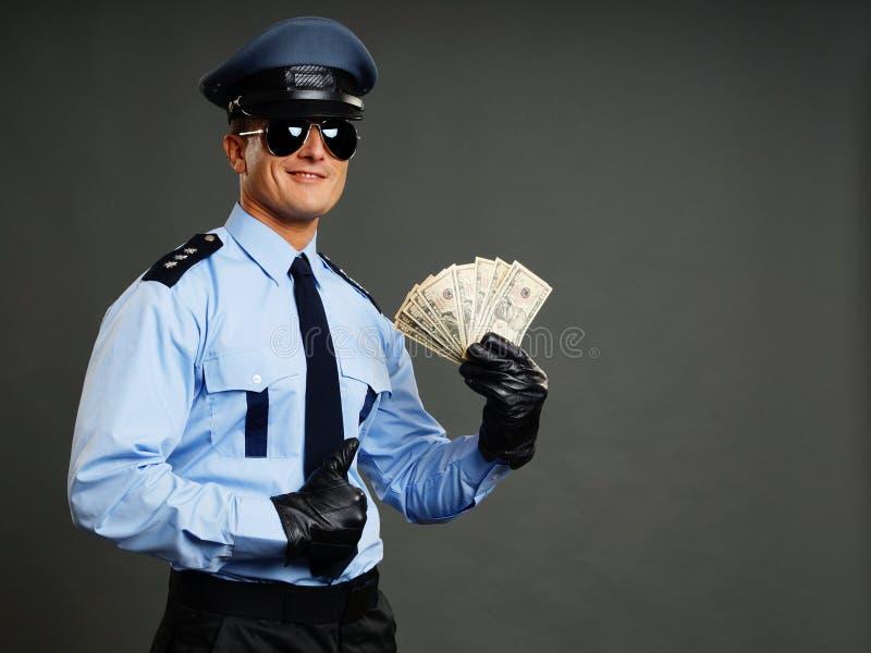 Politieagent met geld stock foto