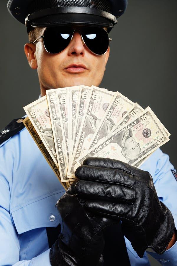 Politieagent met met geld royalty-vrije stock foto's