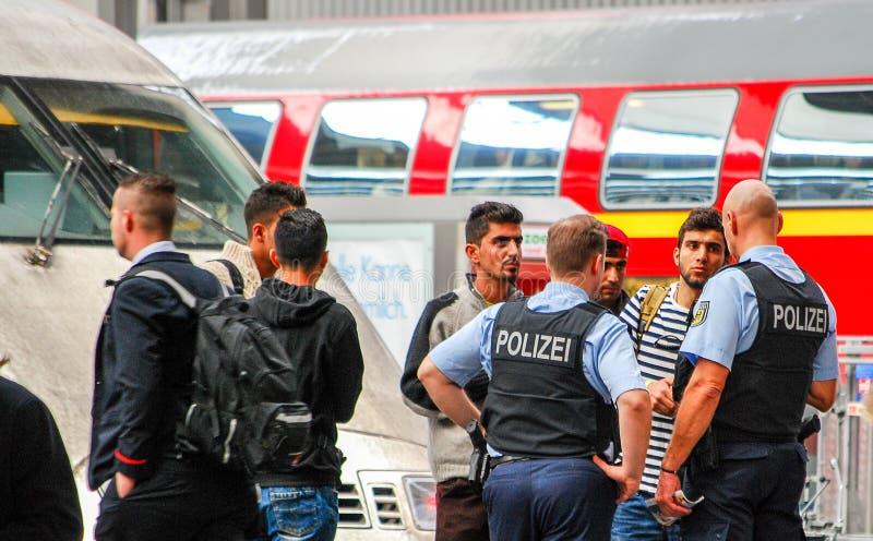 Politiebespreking aan verscheidene migranten die door trein aankwamen stock foto's