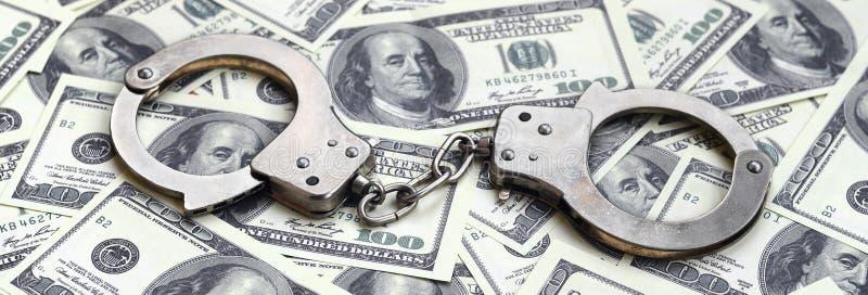 Politiehandcuffs liggen op heel wat dollarrekeningen Het concept onwettig bezit van geld, onwettige transacties met Amerikaanse d royalty-vrije stock foto's