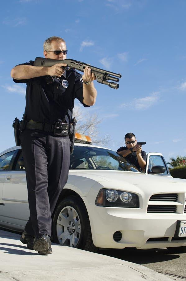 Politieman Aiming Shotgun stock foto's