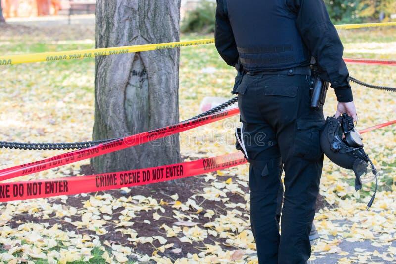 Politieman in de helm die zich door de misdaadscène bevinden royalty-vrije stock fotografie