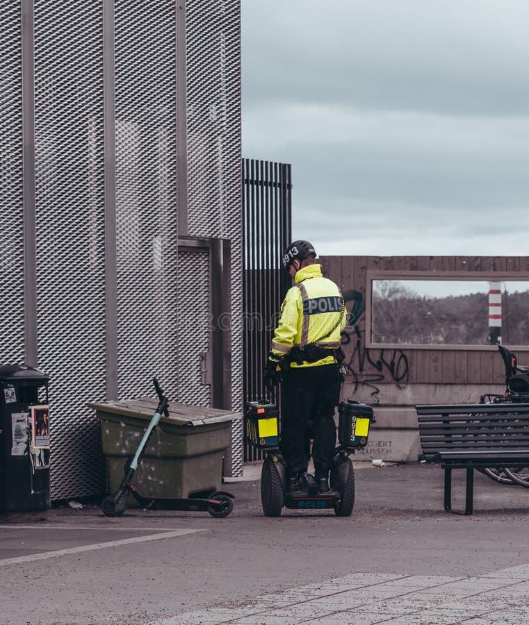 Politieman op een Segway die de straten patrouilleren en een schopfiets inspecteren stock foto's