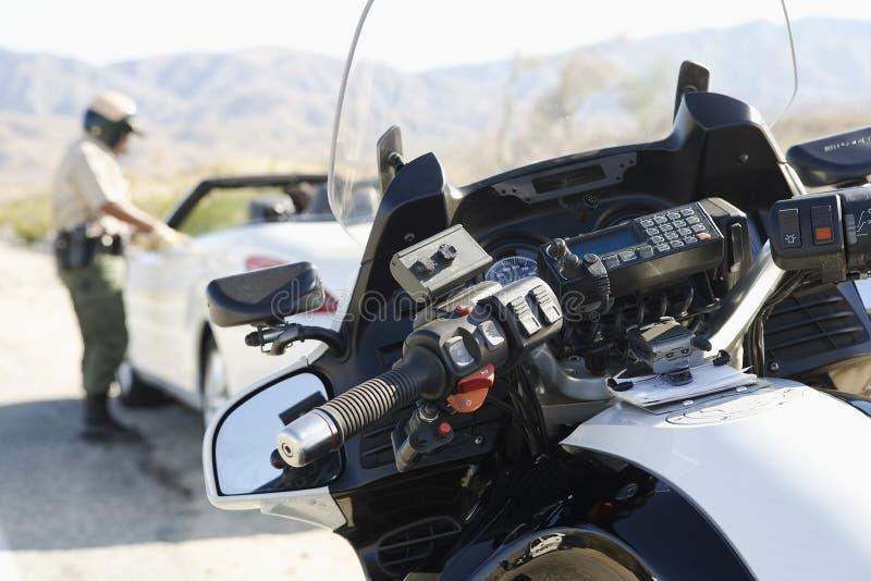 Politieman Talking To Driver van Tegengehouden Auto stock afbeeldingen
