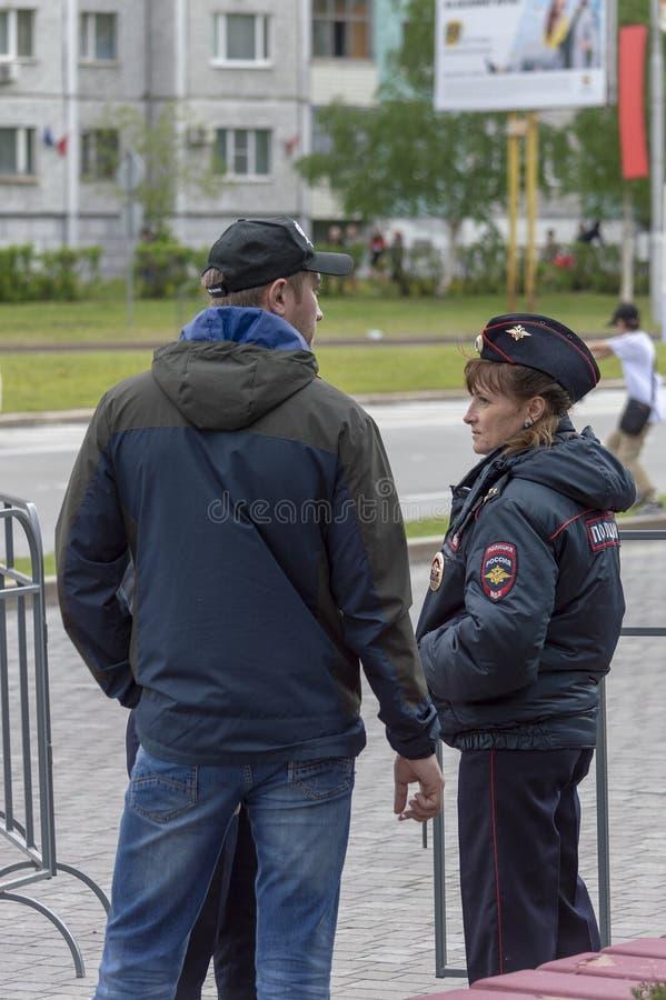 Politiemeisje die op de straat met mensen spreken stock fotografie