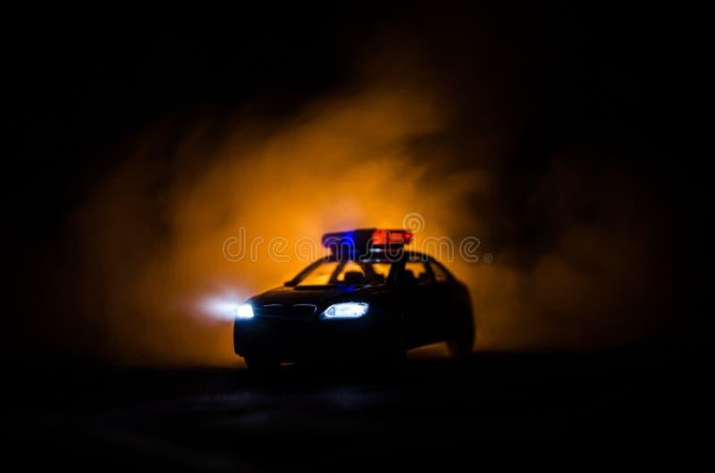Politiewagen die een auto achtervolgen bij nacht met mistachtergrond 911 de politiewagen van de noodsituatiereactie het verzenden stock foto's
